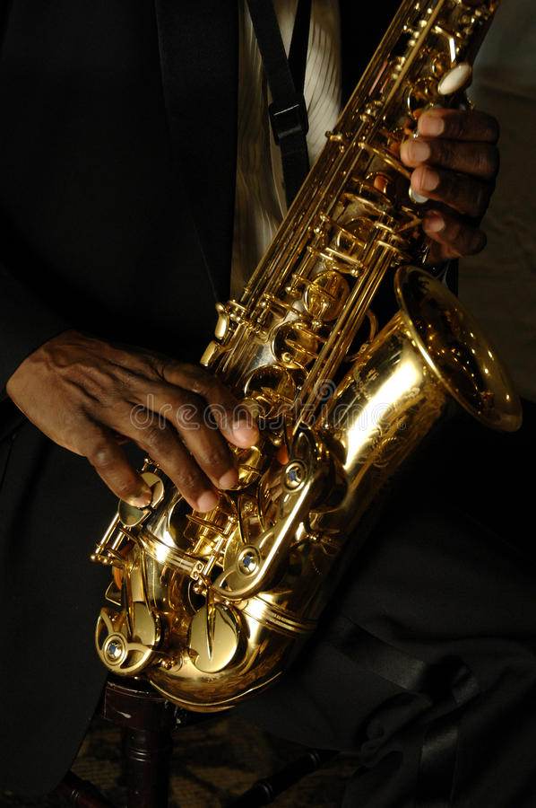 Hands and saxophone. Fingers playing a saxophone against black stock photo