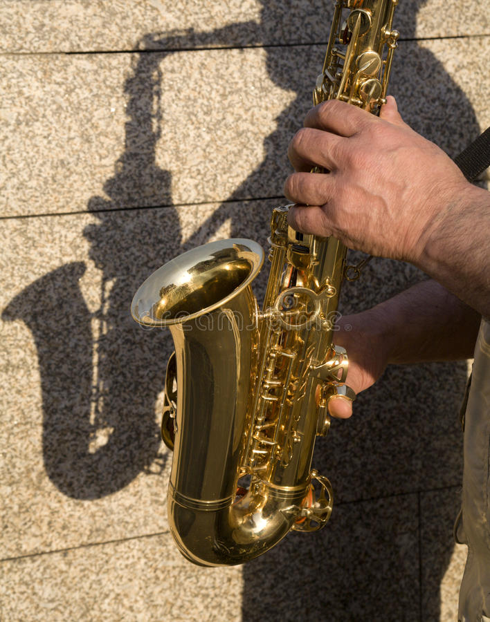 Hands of saxophone player. And shadow stock photo