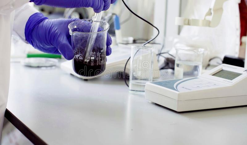 Hands of a scientist measuring pH of the sample royalty free stock photo
