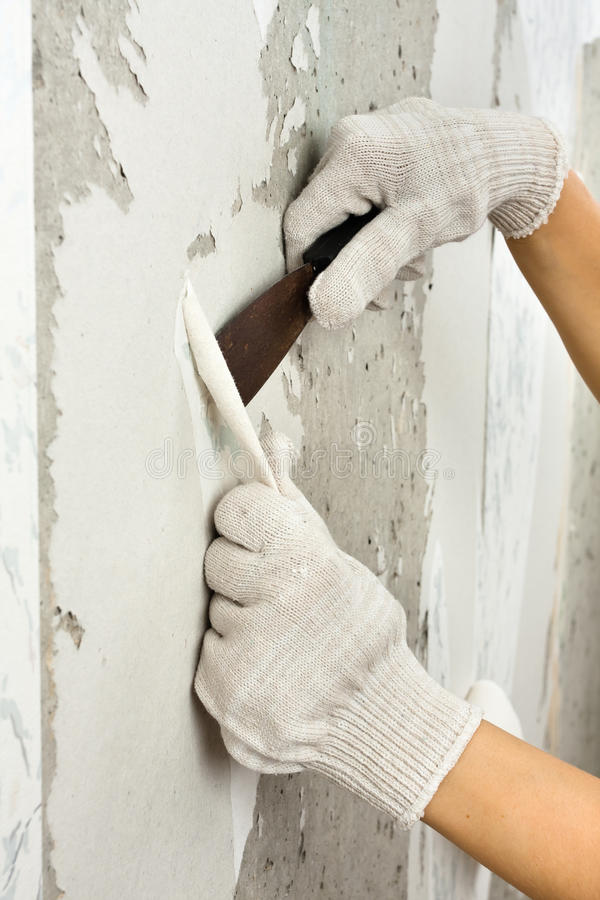 Download Hands Scraping Off Old Wallpaper With Spatula During Repair Stock Image