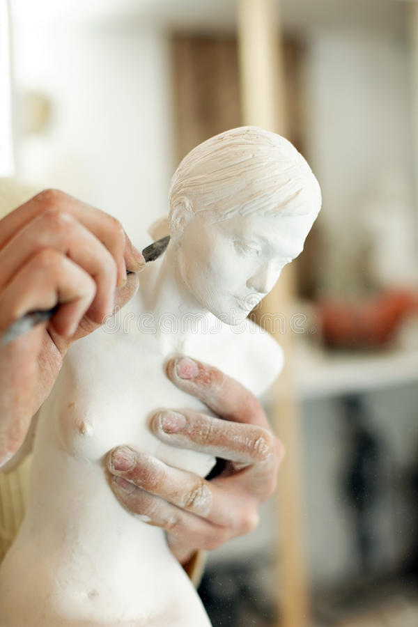 Hands of sculptor with statuette. And a tool with which he works on plaster royalty free stock photo