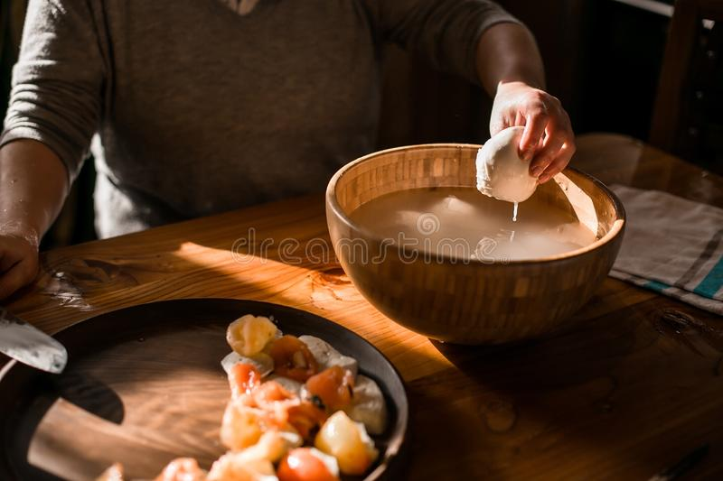 The hands sell the mozzarella from brine royalty free stock image