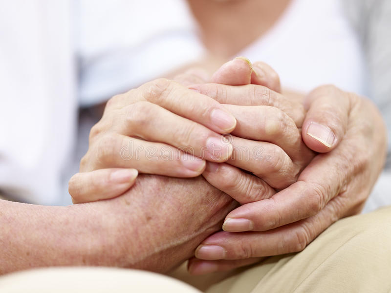 Hands of a senior couple held together royalty free stock photos
