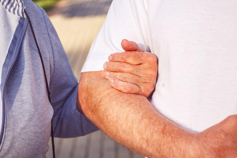 Hands of senior couple during walk in park on sunny day - Happy together stock photos