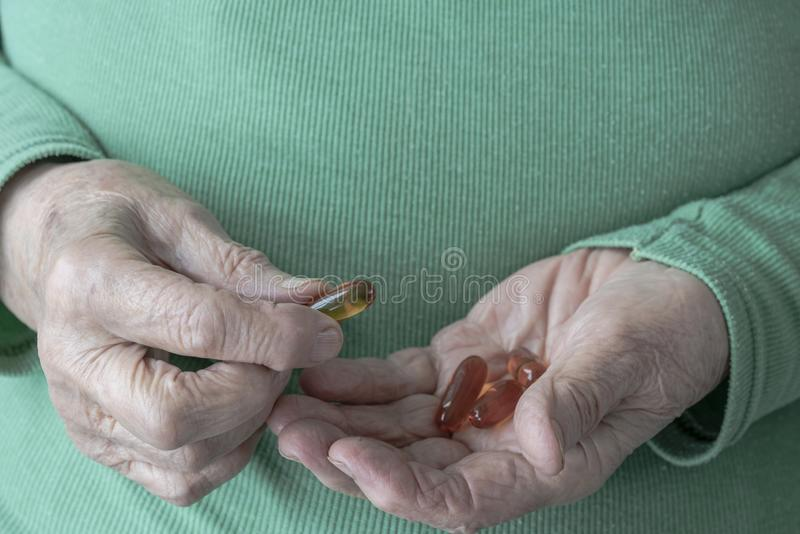 Hands of a senior woman holding vitamin pills on her palm royalty free stock image
