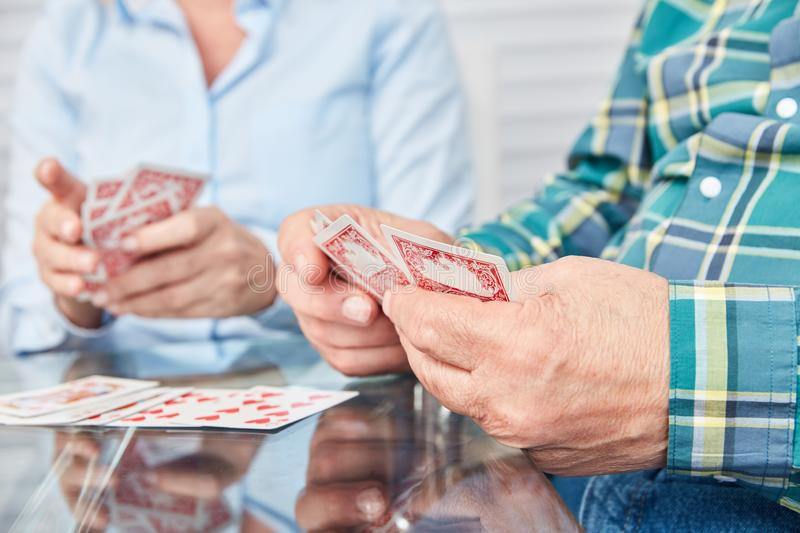 Hands of seniors are holding cards. Hands of seniors holding cards while playing cards in the retirement home stock photography