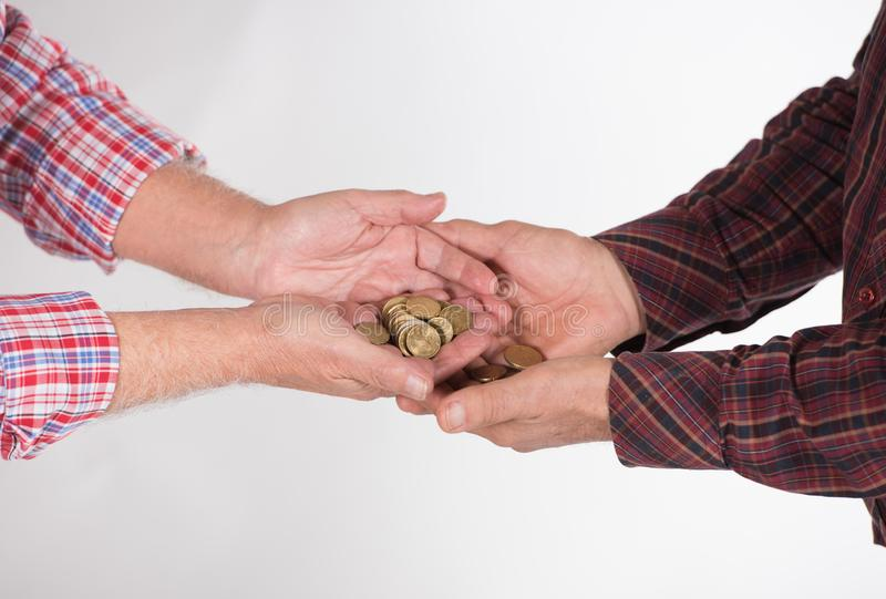 Elderly men with euro money. Hands in shirts of two elderly men holding golden euro coins royalty free stock image