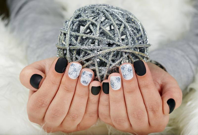 Hands with manicured nails colored with black and white nail polish. Hands with short manicured nails colored with black and white nail polish and Christmas ball royalty free stock photography