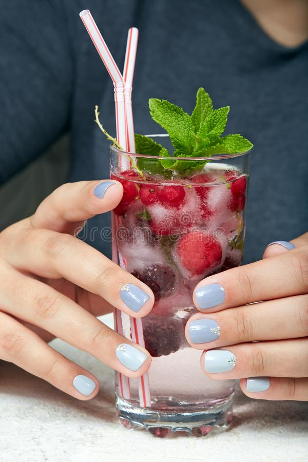 Hands with short manicured nails colored with gray nail polish. And a glass of cold lemonade with berries royalty free stock photo