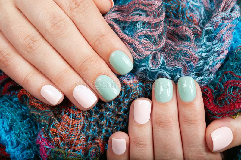 Hands with short manicured nails colored with pink and green nail polish. On textile background stock photos