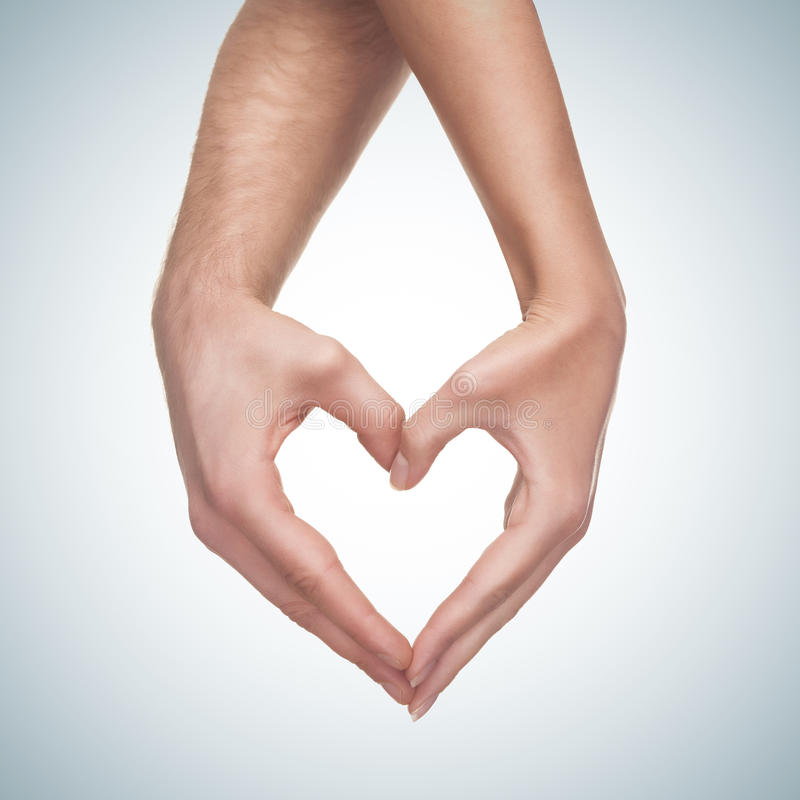 Hands show heart gesture. Man and woman hands show heart gesture on blue gradient background royalty free stock photo