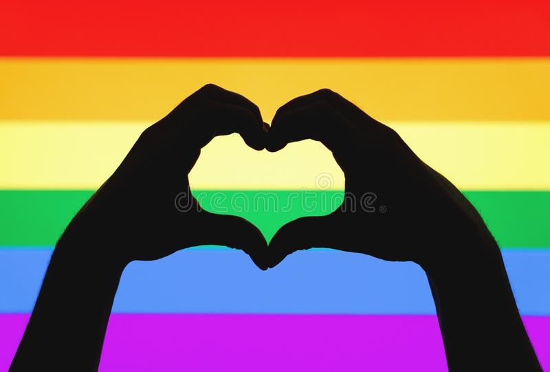 Hands showing heart sign on gay pride and LGBT rainbow flag. Sexual minority, homosexuality and equal rights concept. Silhouette of love symbol on colorful royalty free stock image
