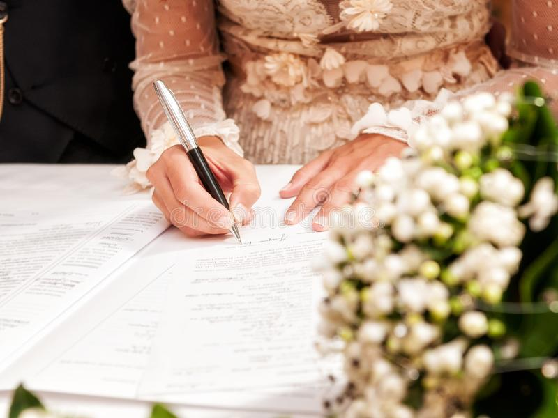 Hands signing during the wedding. Detail of the hand of a bride who signs the marriage act stock images