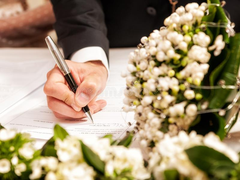 Hands signing during the wedding. Detail of the hand of a groom who signs the marriage act royalty free stock photos