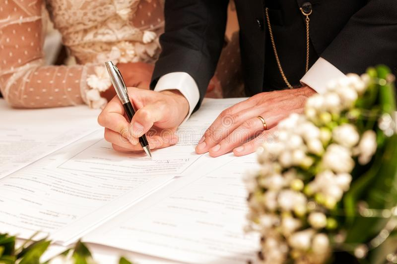 Hands signing during the wedding. Detail of the hand of a groom who signs the marriage act stock photo