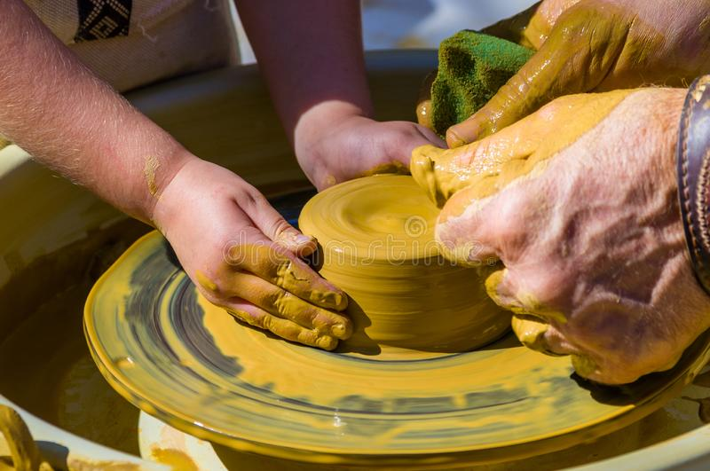 Hands of the skilled master Potter and children's hands, training of the kid to production of pottery on a Potter's wheel. Close-up royalty free stock photos