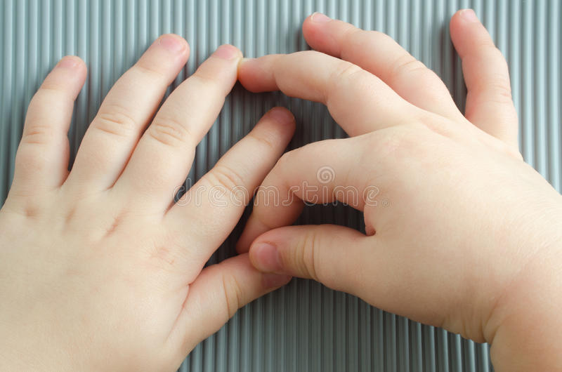 Hands of a small child. Along on a gray striped background stock photography