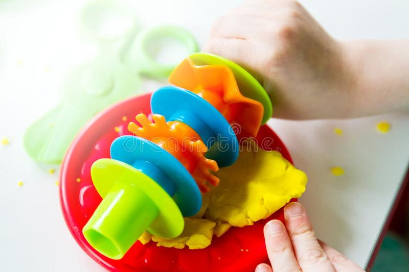 Hands of small child rolling play dough on a tray stock photo