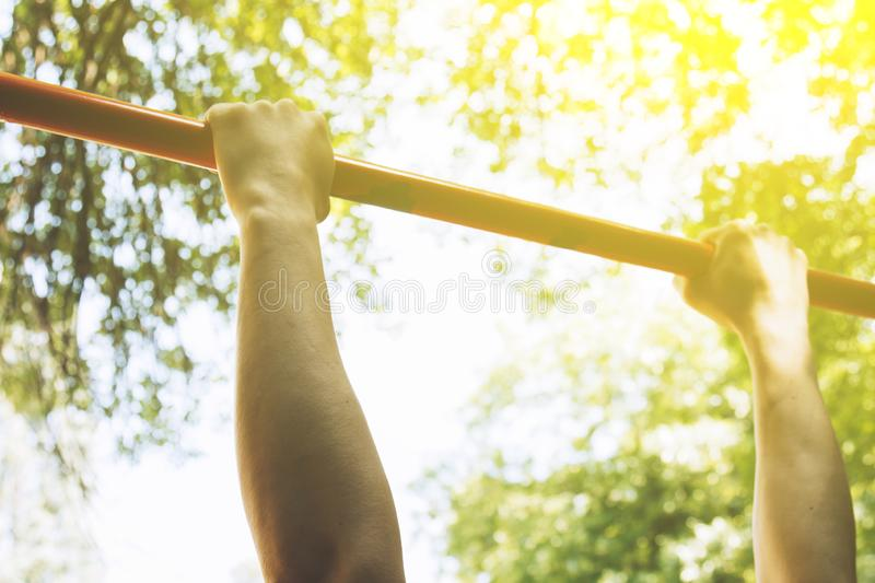 The hands of a sports athlete hold on to a metal crossbar for pull-ups on the training ground against a clear sky and green. Foliage. sports training outdoors stock photo