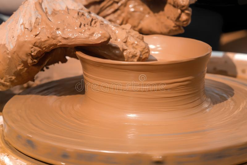 Hands of a street potter make a clay pot on a potter`s wheel. Close-up royalty free stock photos