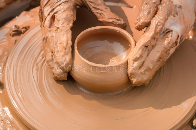 Hands of a street potter make a clay pot on a potter`s wheel. Close-up royalty free stock photo