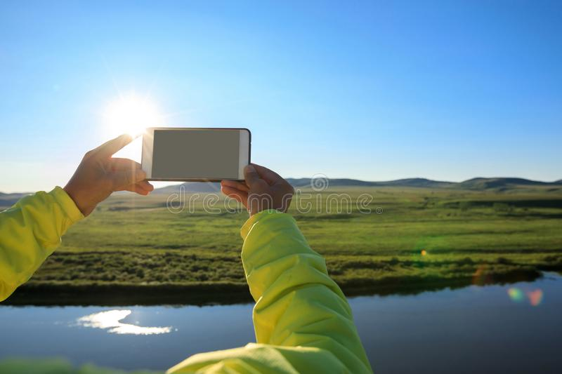 Hands taking photo with smart phone. In beautiful landscape royalty free stock images