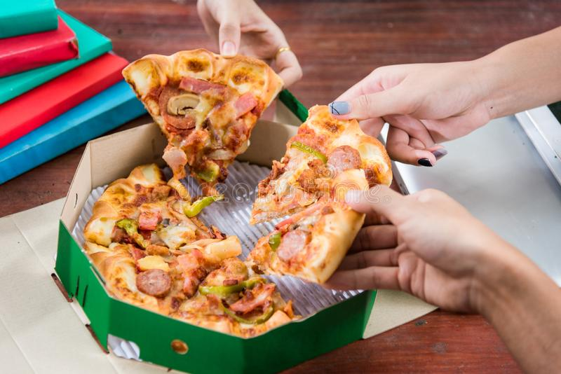 Hands taking pizza slices royalty free stock image