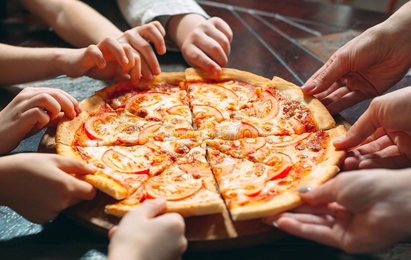 Hands taking pizza slices from wooden table, close up view. royalty free stock image