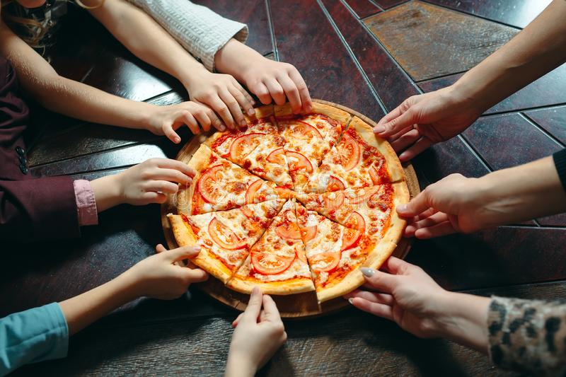 Hands taking pizza slices from wooden table, close up view. stock image