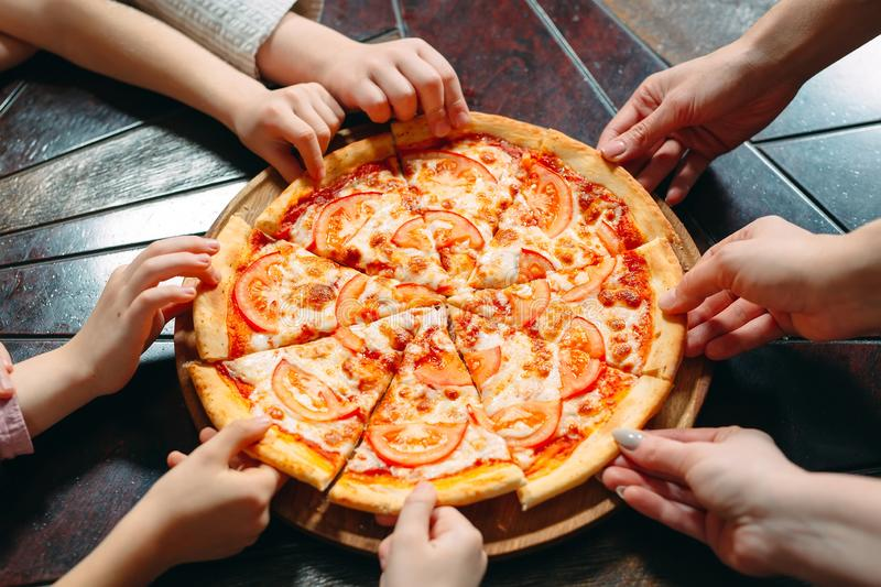 Hands taking pizza slices from wooden table, close up view. royalty free stock photo