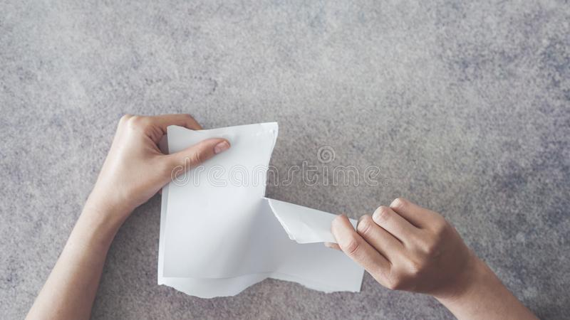 Hands tear paper high angle view royalty free stock image