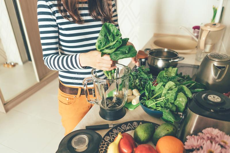 Hands tearing spinach leaves into a blender bowl stock images