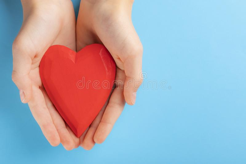 Hands of a teenager child holding a red wooden heart in their hands. Blue background stock image