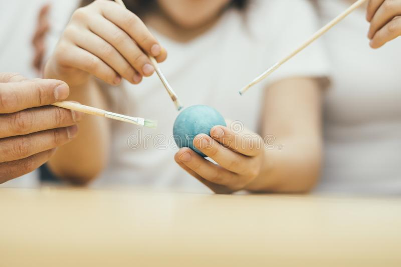 Hands with three painbrushes colouring blue easter egg. Happy family. Easter mood. Focus on the egg. stock photography