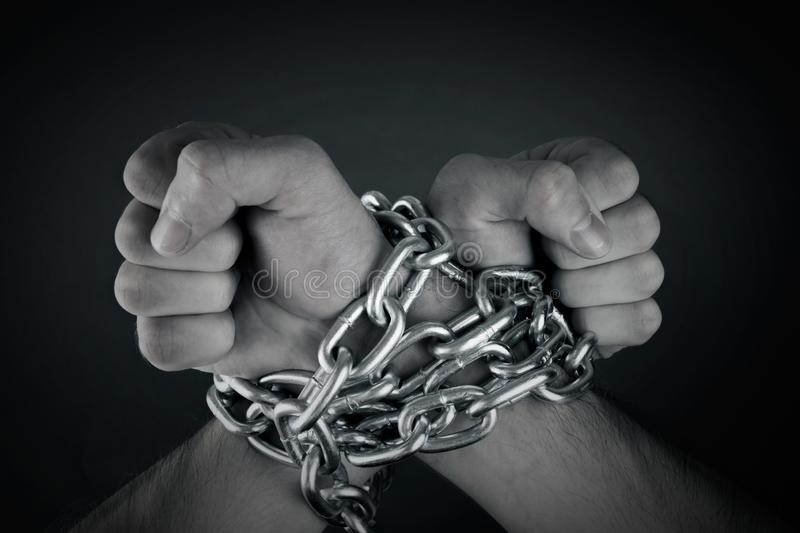 Hands tied with chains stock images