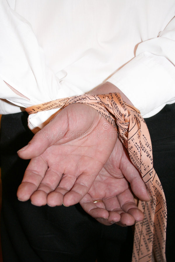 Hands Tied On The Deal. Buisinessman with hands tied behind back with his stock market tie royalty free stock image