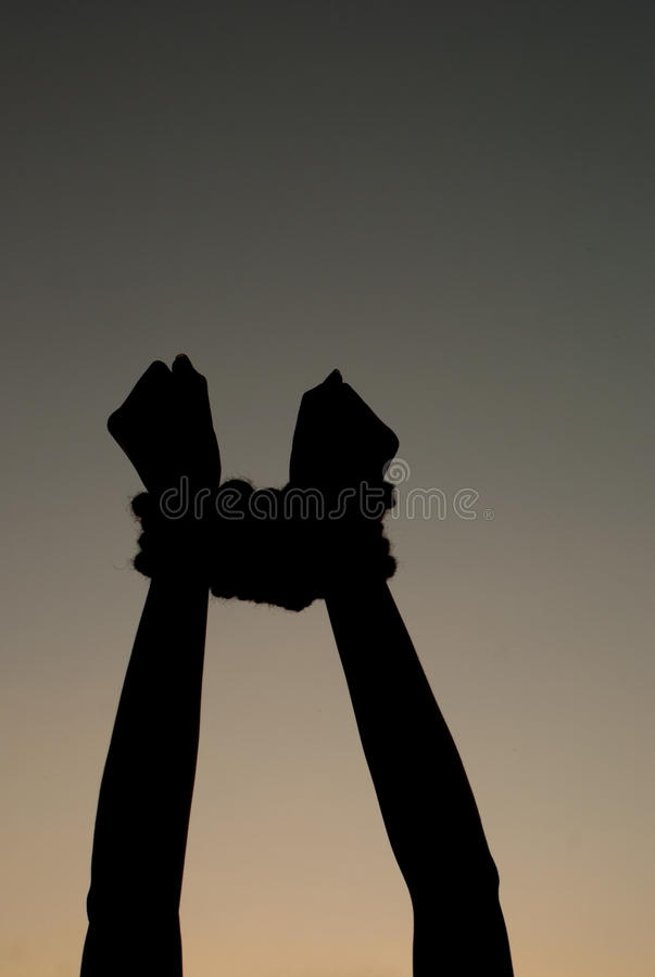 Hands tied up with rope. Against dark sky royalty free stock images