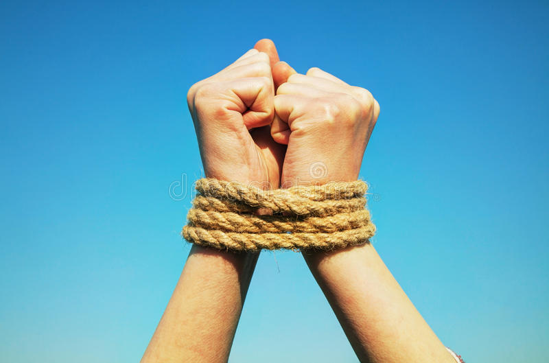 Hands tied up with rope. Against blue sky stock photography