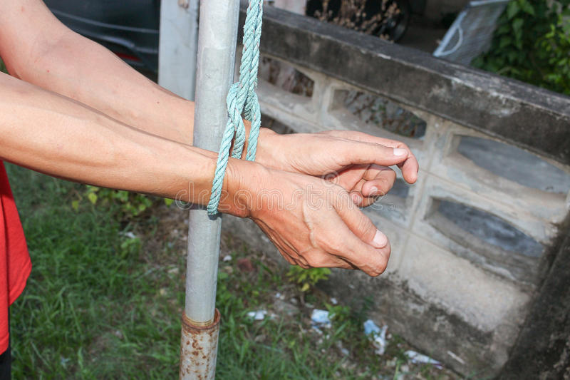 Hands tied up with rope, male with post steel hands tied rope stock image
