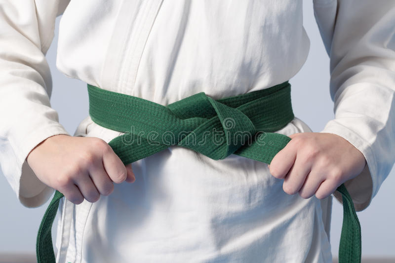 Hands tightening green belt on a teenage dressed in kimono. For martial arts royalty free stock photography