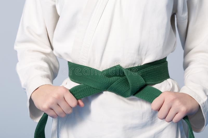 Hands tightening green belt on a teenage dressed in kimono. For martial arts royalty free stock images