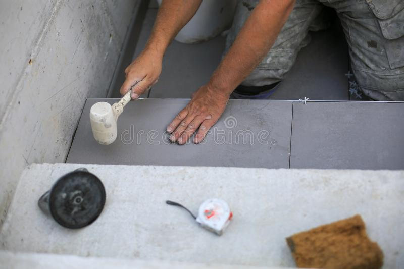 The hands of the tiler are laying the ceramic tile on the floor. stock image