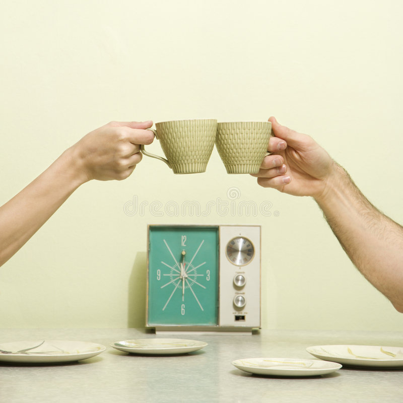 Hands toasting cups. Caucasian male and female hands toasting with coffee cups across retro kitchen table setting royalty free stock images