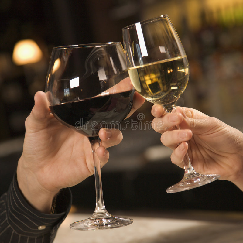 Hands toasting wine. Mid adult Caucasian male and female hands toasting wine glasses stock image