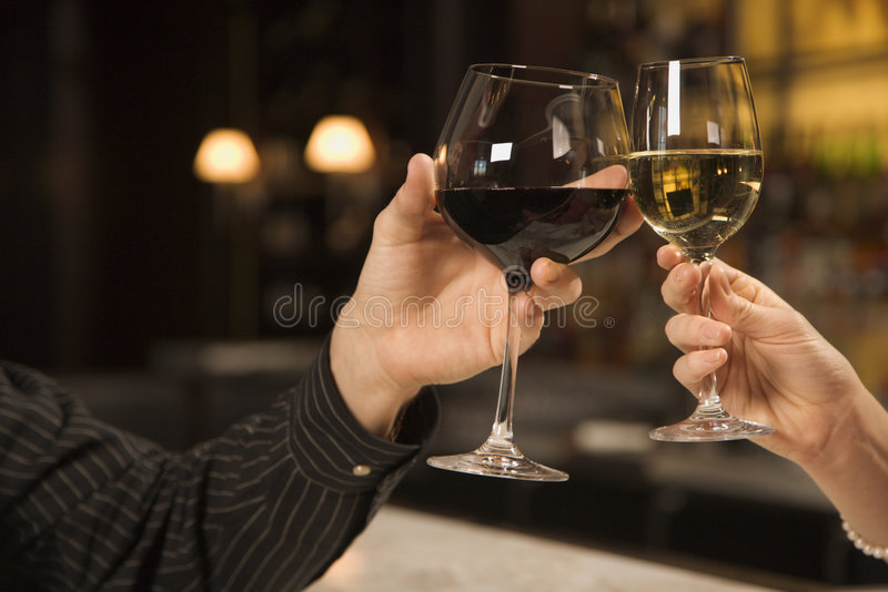 Hands toasting wine. Mid adult Caucasian male and female hands toasting wine glasses stock photography