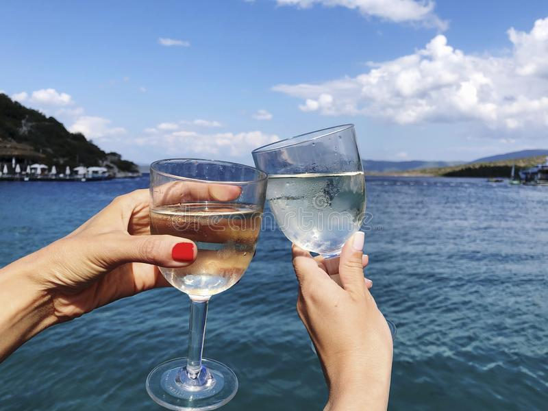Toasting wine glasses against sea and sky in summer. Hands toasting wine glasses against sea and sky in summer royalty free stock photos