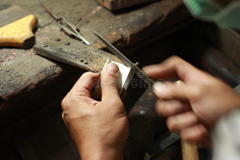 hands and tools of a professional silversmith working on a piece in his traditional workshop, Northern Thailand stock image