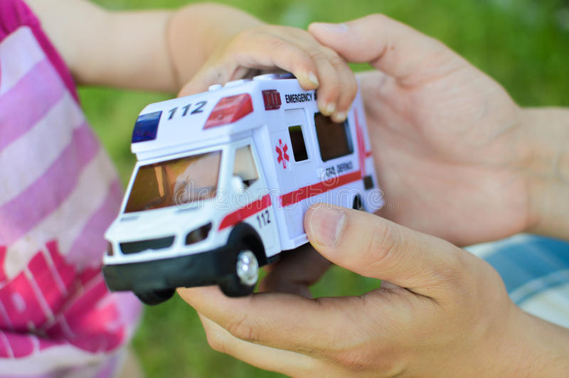 Hands and toy car showing concept of lifesaving. A human hand giving a toy car with the word emergency over it it to a child demonstratiing concept of lifesaving royalty free stock images