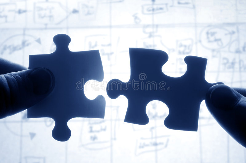 Hands trying to fit two puzzle royalty free stock photography