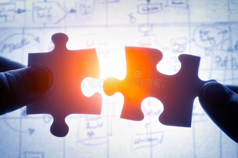 Hands trying to fit two puzzle pieces together royalty free stock photography